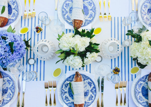A Bastille Day tablescape with blue and white hydrangeas on a striped tablecloth.