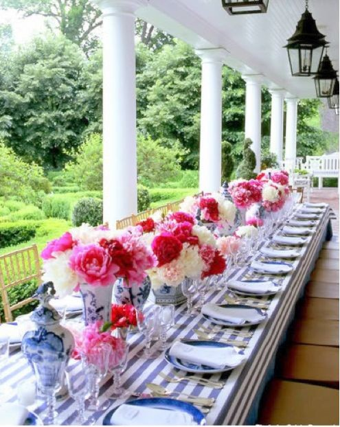 A Carolyne Roehm tablescape featuring pink and red garden roses in blue and white porcelain vases on a striped tablecloth.