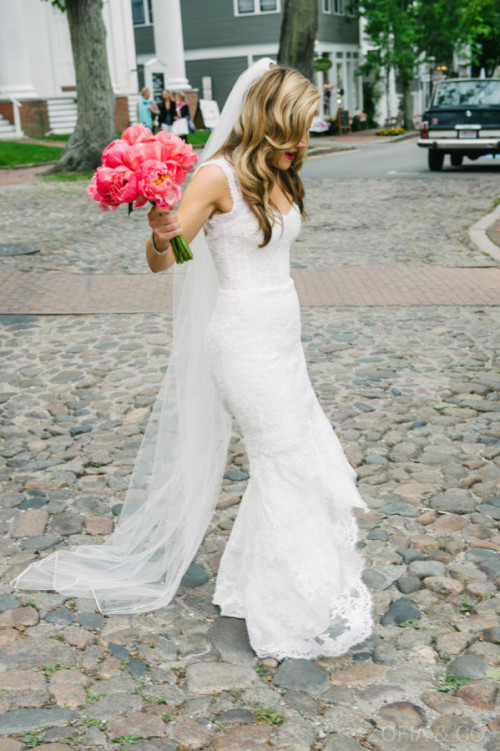 A Nantucket bride carries a bouquet of coral pink peonies on Main Street.