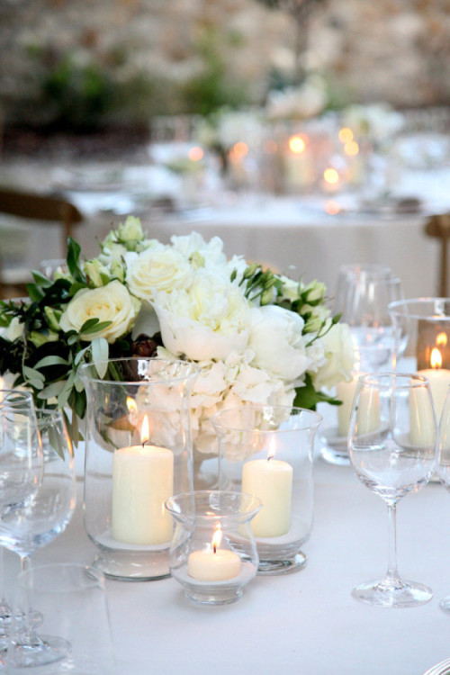 A white wedding centerpiece with hydrangeas, roses, and candles in glass hurricanes.