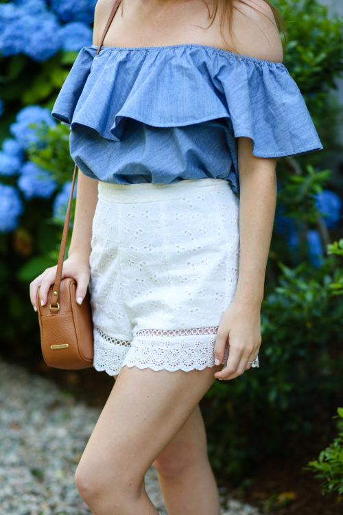 chambray off the shoulder top with tan crossbody bag and white eyelet shorts on design darling