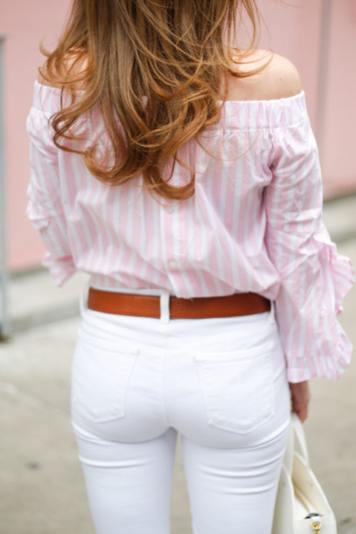 pink and white ruffle sleeve off the shoulder top with white jeans on design darling