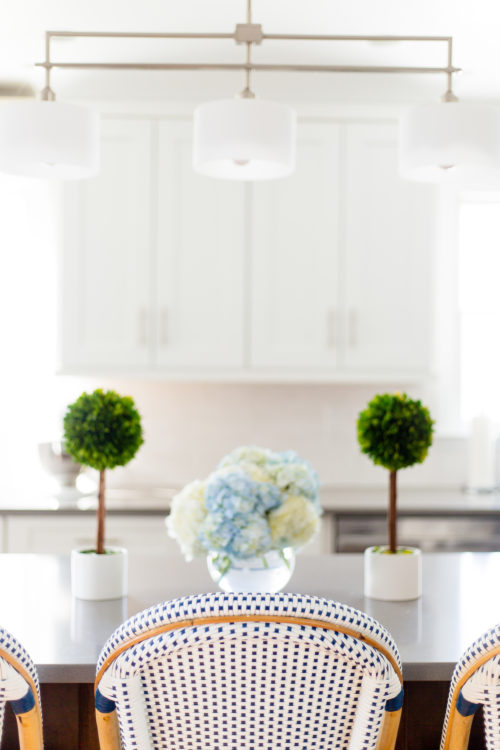 serena & lily riviera counter stool and boxwood topiaries in design darling kitchen