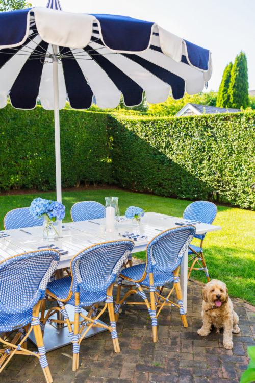 design darling nantucket backyard serena & lily eastport striped umbrella and frontgate paris bistro side chairs in capri blue