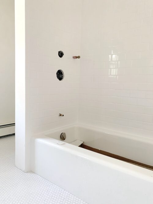 white subway tile in shower with white penny tile on floors