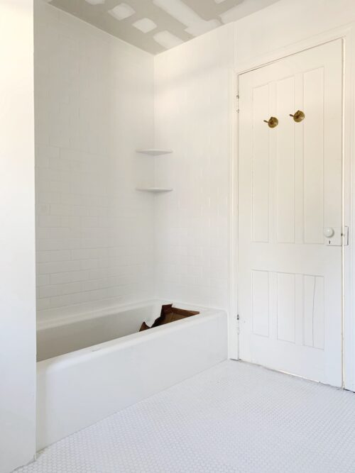 white subway tile shower with white penny tile floors