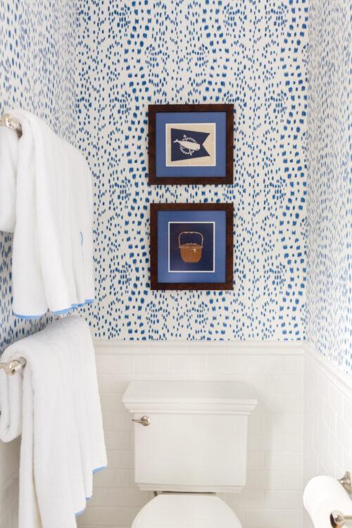 framed needlepoint canvases in design darling hall bathroom.jpg