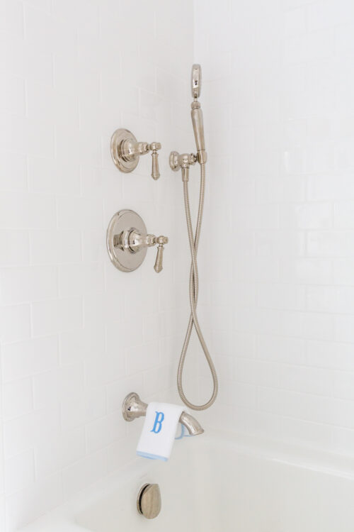 kohler artifacts shower system in polished nickel with white subway tile